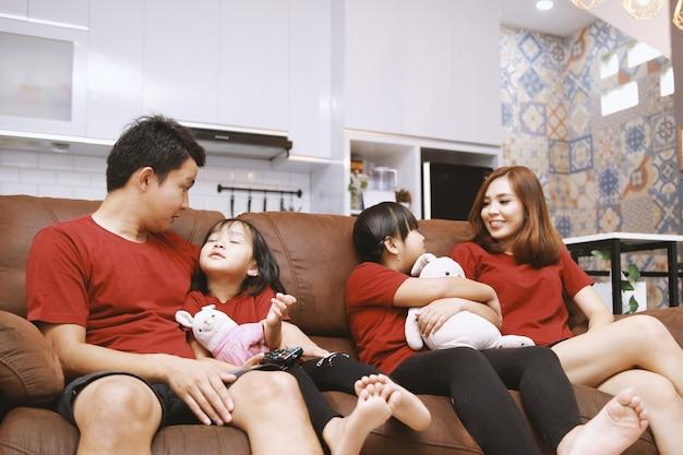 Glückliche eltern und kinder, die spaß haben, zusammen auf dem sofa zu sitzen, fröhliches junges paar, das mit zwei kleinen töchtern im wohnzimmer zu hause lustige aktivitäten der familie spricht und lachen spielt