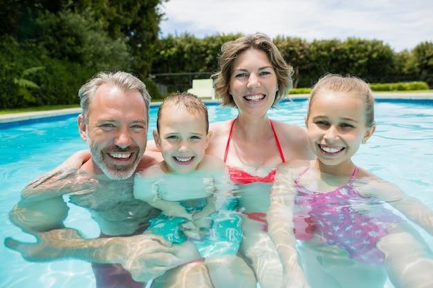 Glückliche eltern und kinder im pool