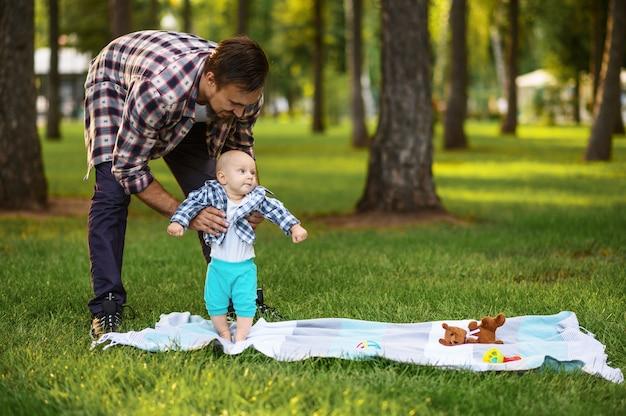 Glückliche eltern und kleines baby spielen auf gras im sommerpark