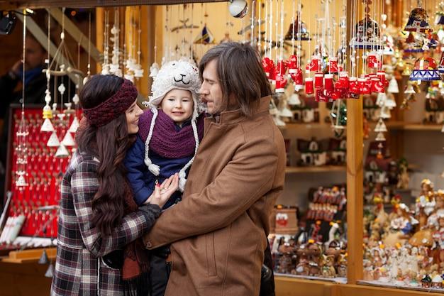 Glückliche eltern und kleines childl am traditionellen europäischen weihnachtsstraßenmarkt