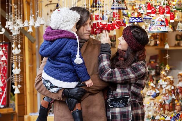 Glückliche eltern und kleines kind, die handgemachte glocke am traditionellen europäischen weihnachtsstraßenmarkt aufpasst. familie mit dem kind, das für geschenke auf winter angemessen kauft. reise, tourismus, feiertage und leutekonzept.