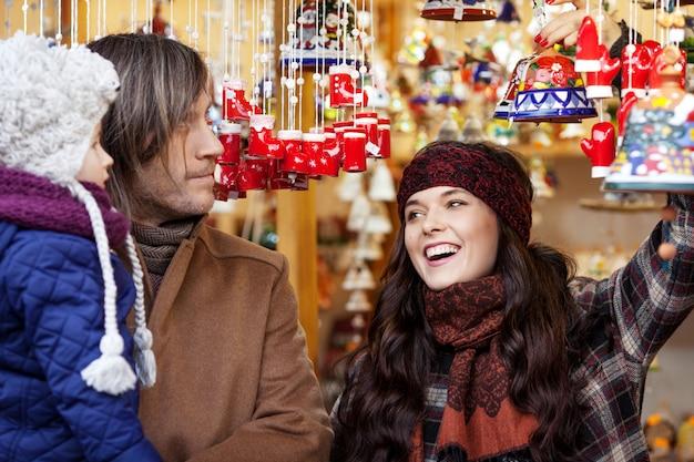 Glückliche eltern und kleines kind, die handgemachte glocke am traditionellen europäischen weihnachtsstraßenmarkt aufpasst. familie mit kind einkaufen für weihnachtsgeschenke. reisen, tourismus, urlaub und menschen.