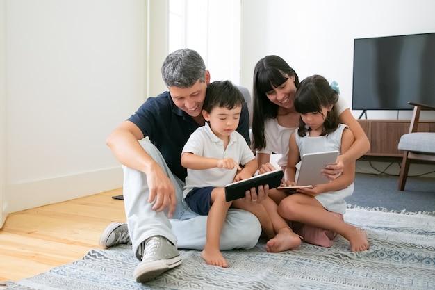 Glückliche eltern und niedliche kinder, die mobile geräte auf dem boden im wohnzimmer verwenden.