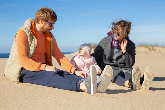 Glückliche eltern und niedliches baby tragen warme kleidung, genießen freizeit auf see, sitzen zusammen auf sand