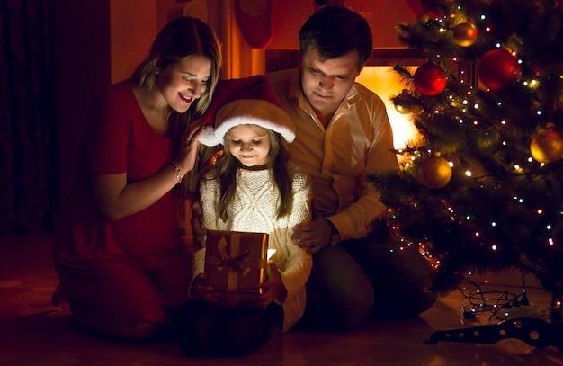 Glückliche eltern und süße tochter, die in das weihnachtsgeschenk schaut