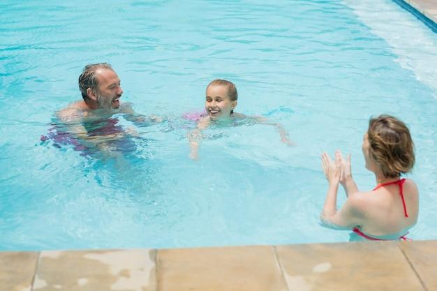 Glückliche eltern und tochter, die spaß im pool haben