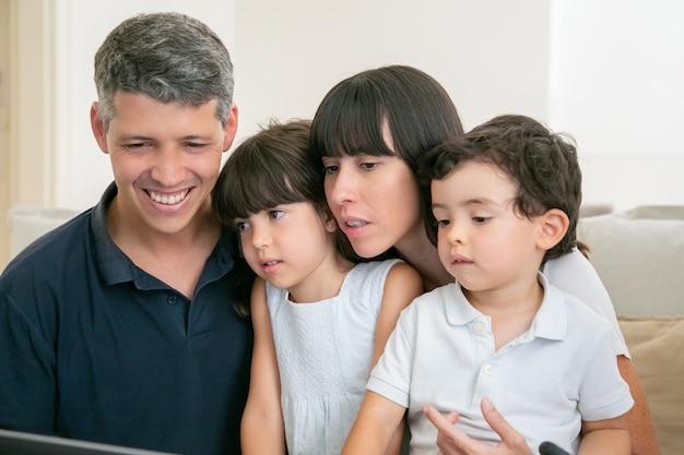 Glückliche eltern und zwei kinder, die computeranzeige betrachten, sitzen auf couch zusammen.