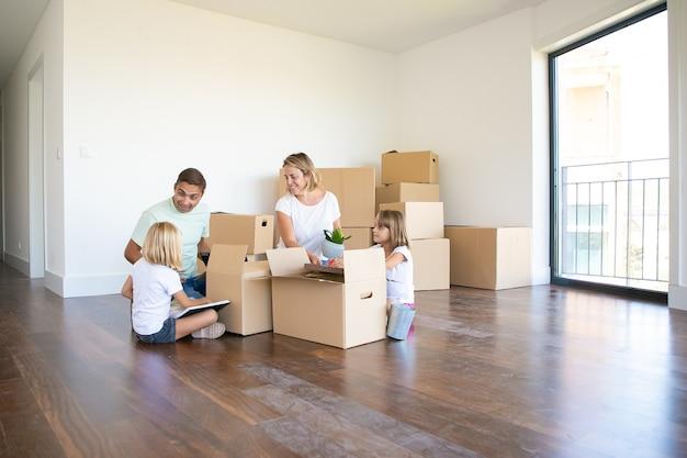 Glückliche eltern und zwei kinder, die in neue leere wohnung einziehen, sitzen auf boden in der nähe offener kisten