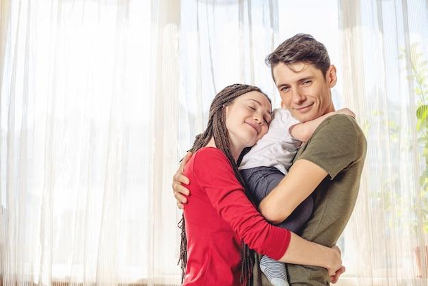 Glückliche eltern vater und mutter, die mit babysohn am fenster spielt. fröhliche und moderne junge familie