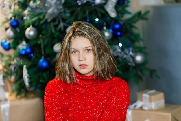 Glückliche emotional überraschte junge frau am weihnachtsbaum im gemütlichen wohnzimmer, konzept des glücks