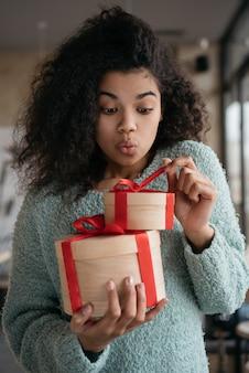 Glückliche emotionale afroamerikanische frau, die geschenkbox öffnet