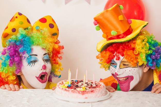 Glückliche emotionale clowns im urlaub, die versuchen, den geburtstagskuchen zu essen