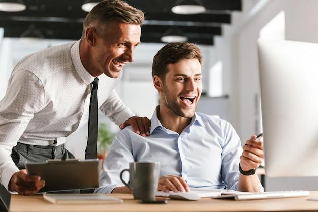 Glückliche emotionale männerkollegen im büro, das mit computer arbeitet.