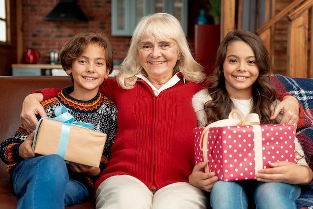 Glückliche enkelkinder des mittleren schusses, die mit großmutter aufwerfen