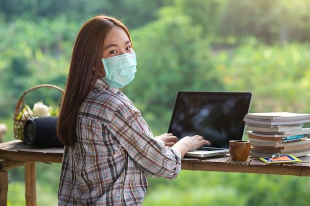 Glückliche entspannte asiatische junge frau, die auf einem laptop mitten in der natur sitzt und medizinische gesichtsmaske trägt und in die kamera schaut, um die ausbreitung des koronavirus zu verhindern.