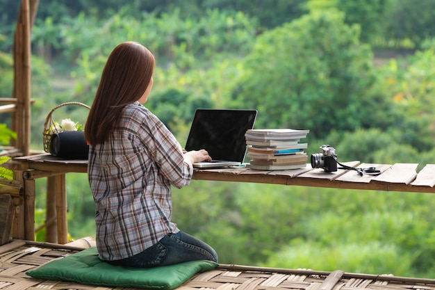 Glückliche entspannte asiatische junge frau, die inmitten der natur an einem laptop sitzt und arbeitet.