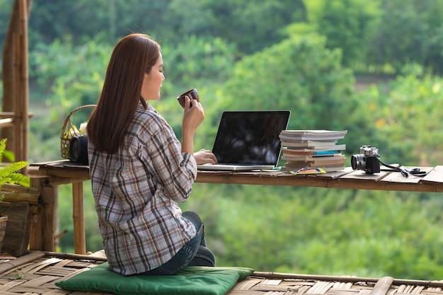 Glückliche entspannte asiatische junge frau sitzen kaffee mitten in der natur mit einem laptop im rücken von ihr trinken und am morgen aus der natur schauen.