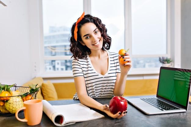 Glückliche entspannungszeit zu hause der freudigen jungen frau mit geschnittenem lockigem haar, das auf tisch im wohnzimmer lächelt. laptop mit grünem bildschirm, zitrus, apfel, magazin, tee, chillen in moderner wohnung