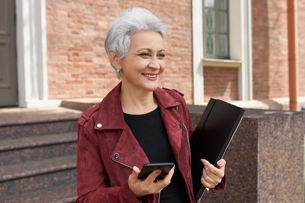 Glückliche erfolgreiche 50-jährige frau in der trendigen jacke, die auf der tür posiert, die smartphone und ordner hält