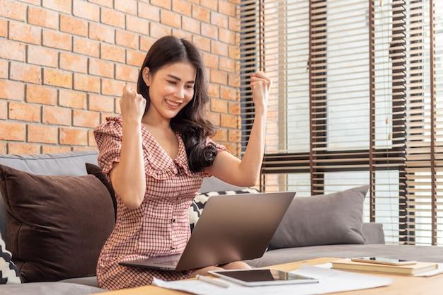 Glückliche erfolgreiche asiatische frau, die aufgeregt beide hände in den fäusten vor ihrem computer in ihrem haus erhebt