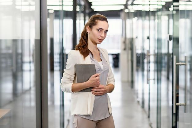 Glückliche erfolgreiche frau mit tablet-computer am modernen bürokorridor.
