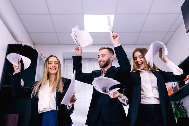 Glückliche erfolgreiche geschäftsleute im büro, die spaß haben, dokumente zu werfen