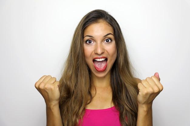 Glückliche erfolgreiche junge frau mit erhobenen händen, die schreien und erfolg feiern