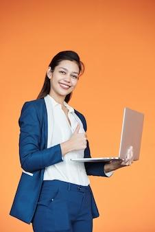 Glückliche erfolgreiche junge geschäftsfrau, die laptop hält und daumen hoch zeigt