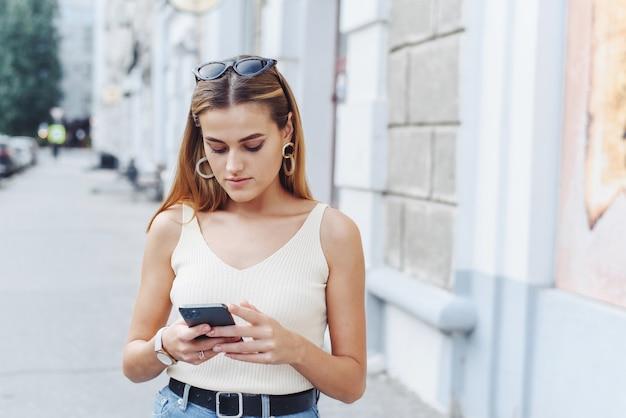 Glückliche erfolgreiche lächelnde frau, die smartphone für das einkaufen online auf straßenhintergrund im freien verwendet. nahansicht.