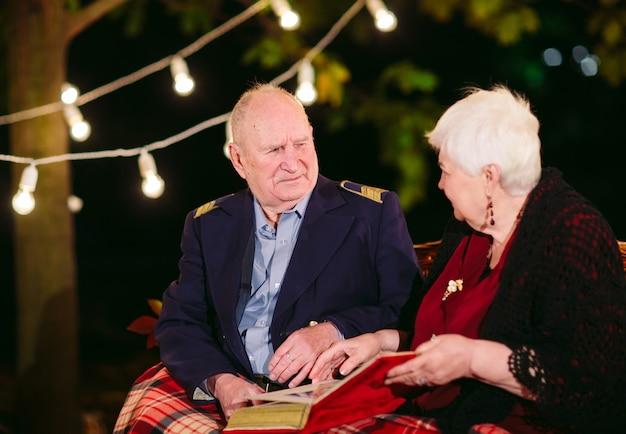 Glückliche erinnerungen. glückliche ältere paare, die auf überwachendem album des sofas mit fotos sitzen.