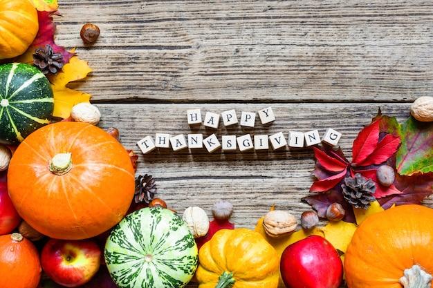 Glückliche erntedank-inschrift auf herbsthintergrund mit geernteten kürbissen, äpfeln, nüssen und ahornblättern