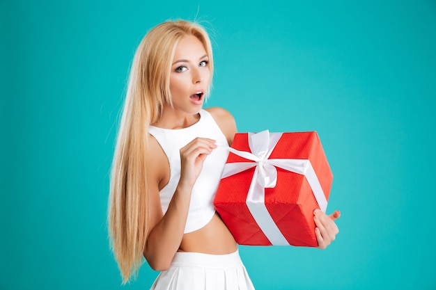 Glückliche erstaunte junge frau, die rote geschenkbox über blauem hintergrund öffnet