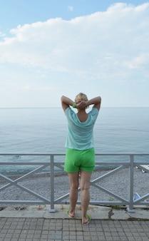 Glückliche erwachsene frau, die gymnastik auf dem strand, hintere ansicht, gesundes lebensstilkonzept tut
