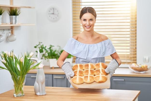 Glückliche erwachsene frau, die heiße kreuzbrötchen für ostern in der küche zubereitet