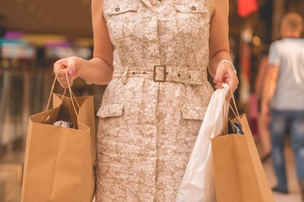 Glückliche erwachsene frau mit einkaufstüten im supermarkt