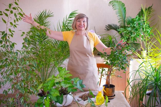 Glückliche erwachsene frau umarmt und pflegt eine topfpflanze pflege von zimmerpflanzen zu hause