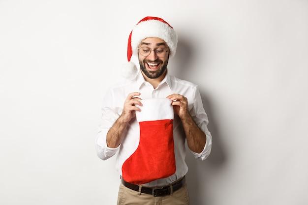 Glückliche erwachsene mann öffnen weihnachtssocke und schauen nach innen, weihnachtsgeschenke für winterferien empfangend, in der weihnachtsmütze stehend