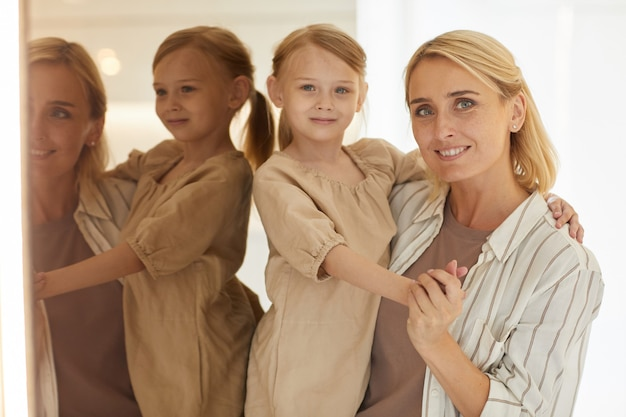 Glückliche erwachsene mutter hält niedliche kleine tochter und lächelt, während sie zu hause am spiegel steht