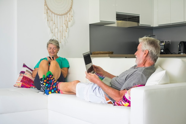 Glückliche erwachsene paare zu hause mit internet-technologie, die sich auf dem sofa niederlegen, sowohl mit laptop als auch mit angeschlossenem telefon