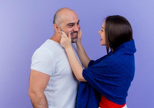 Glückliche erwachsene paarfrau, die in schal gewickelt wird, der die wangen des mannes kneift, die beide lächeln und einander ansehen