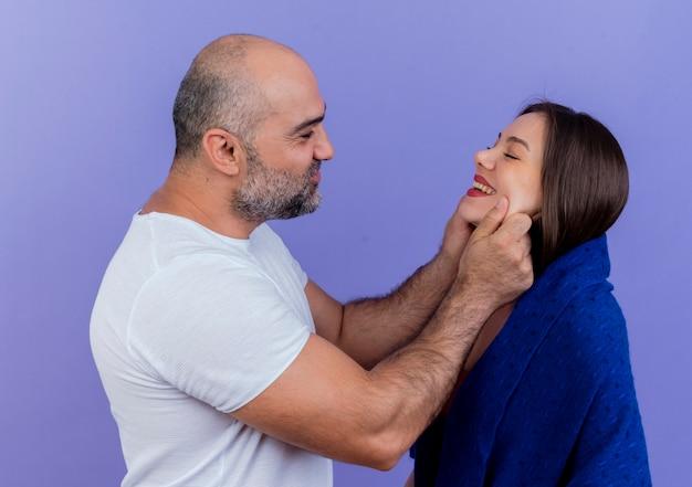 Glückliche erwachsene paarfrau in schal gewickelt, der mit geschlossenen augen lächelnder mann sie ansieht und ihre wangen kneift
