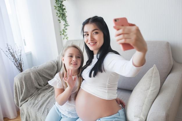 Glückliche erwartende frau, die ihrem ehemann selfie macht. schwangere hausfrau, die mit ihrer familie am handy spricht.