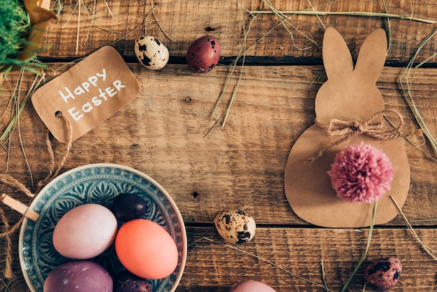 Glückliche ester! draufsicht auf farbige ostereier und osterdekorationen, die auf rustikalem holztisch liegen