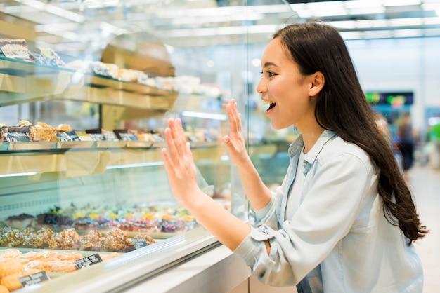Glückliche ethnische frau, die auf süßigkeiten im bäckereispeicher schaut