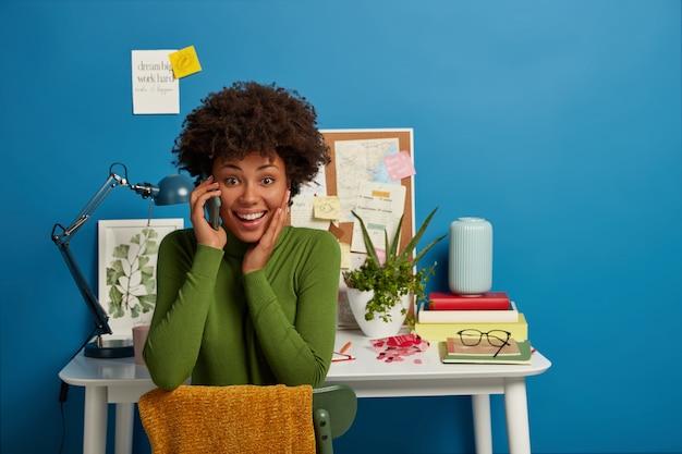 Glückliche ethnische frau hat telefongespräch, hält handy in der nähe des ohrs, freut sich über gute nachrichten, trägt grünen rollkragenpullover, sitzt auf einem bequemen sofa im gemütlichen arbeitszimmer, bespricht die neuesten nachrichten