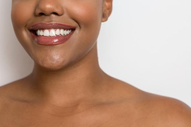 Glückliche ethnische frau mit weicher haut und zahnigem lächeln