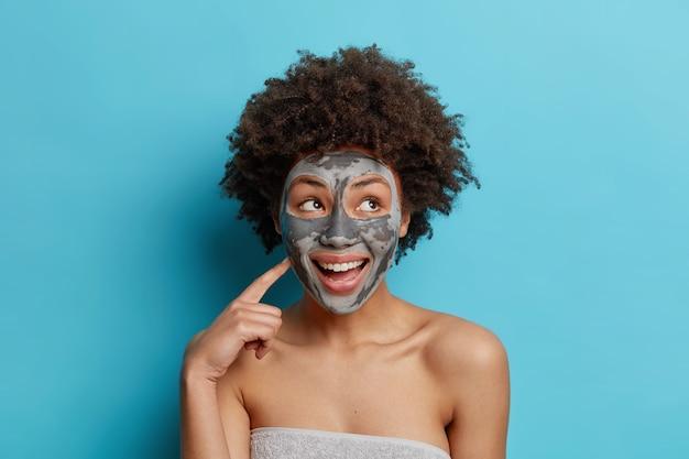 Glückliche ethnische lockige frau lächelt angenehm wendet gesichtsmaske an und möchte schön aussehen, eingewickelt in ein weiches handtuch, isoliert über der blauen studiowand.