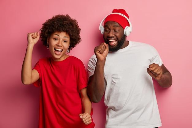Glückliche ethnische tausendjährige mädchen und kerl bewegen sich mit rhythmus der melodie, hören lieblingsmusik, haben fröhliche stimmung, tragen lässige t-shirts. moderne technik, freizeit und freude.
