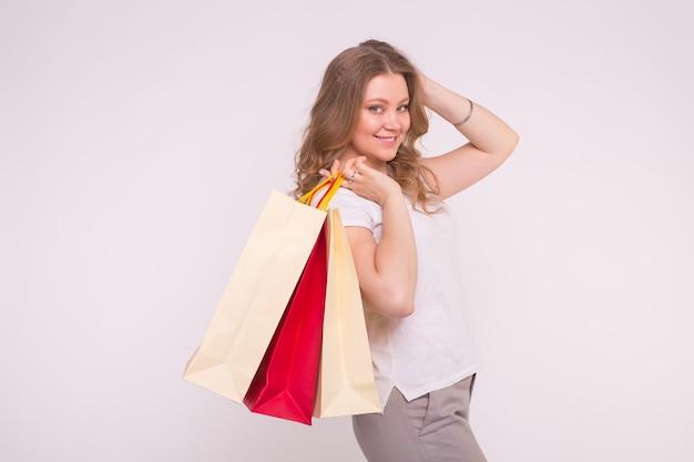 Glückliche europäische blonde frau, die einkaufstaschen auf weiß mit kopienraum hält