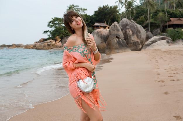 Glückliche europäische frau mit langen haaren im stilvollen boho-sommerkleid, das im tropischen strand aufwirft.